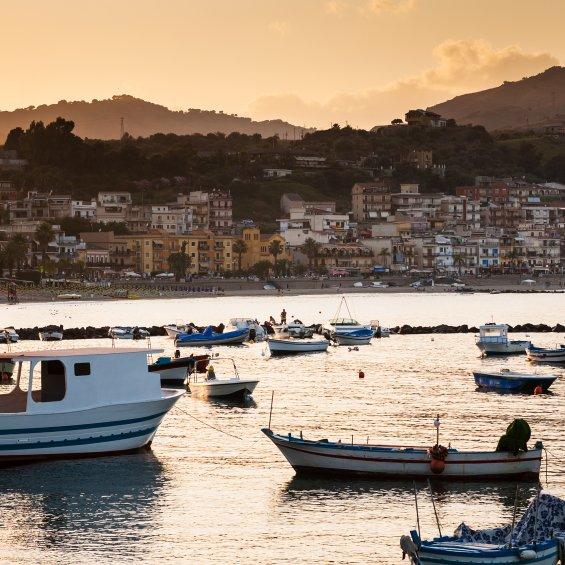 Vista di Giardini Naxos dal mare con pescherecci, provincia di Messina, Sicilia, Italia